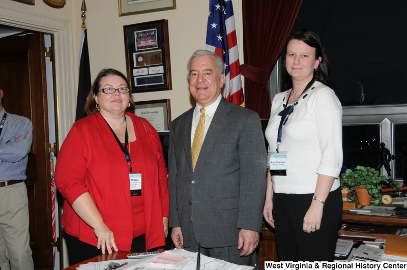 Congressman Rahall stands in his Washington office with two women wearing name badges, including Amy Saunders, Marshall University.
