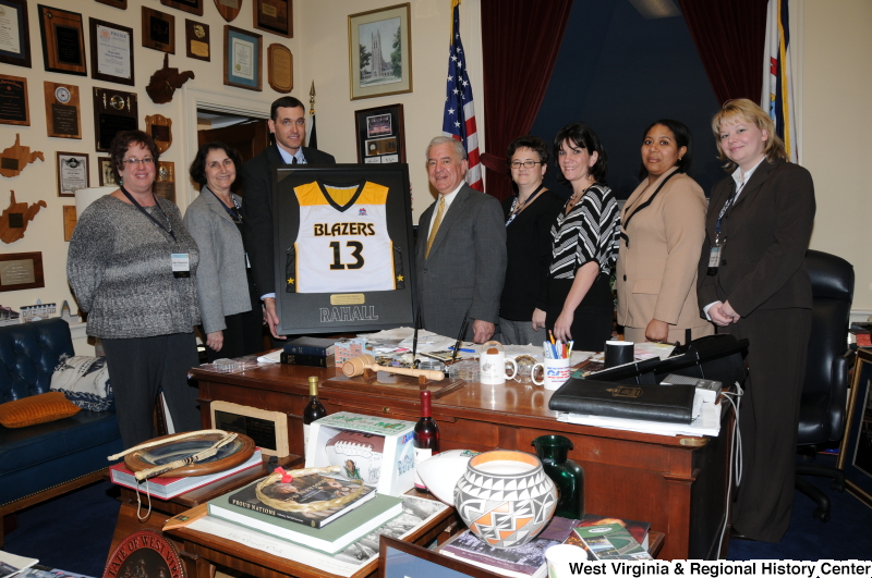 Congressman Rahall stands with a framed West Virginia Blazers jersey and seven other people in his Washington office.