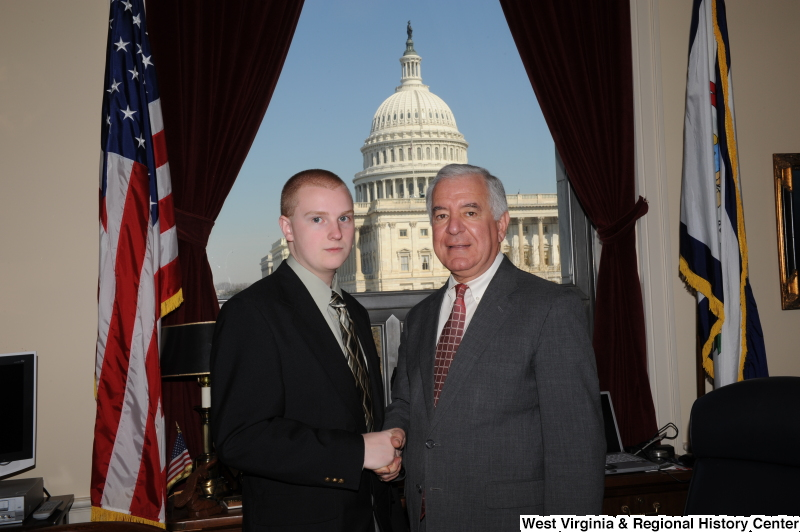 Congressman Rahall shakes hands with a young man in his Washington office.