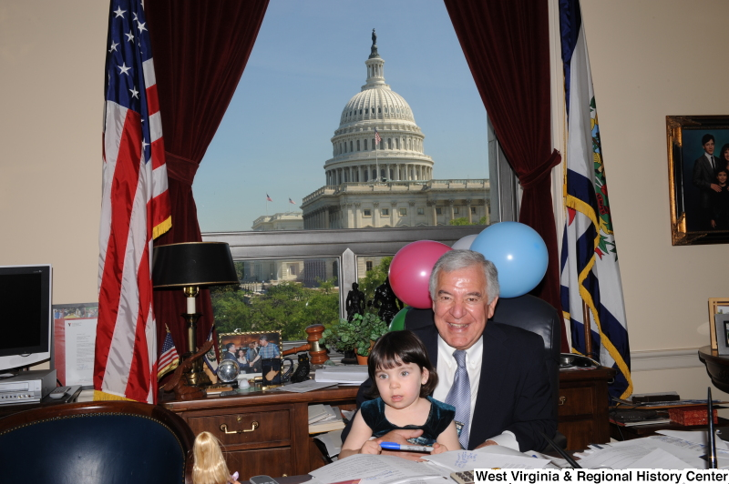 Congressman Rahall sits in his Washington office with a girl and balloons.