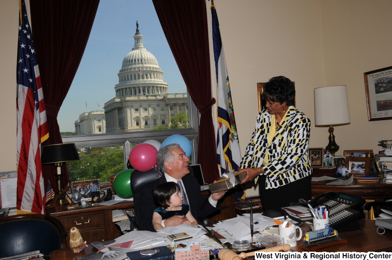 Congressman Rahall sits in his Washington office with a girl, balloons, and a woman holding a present.