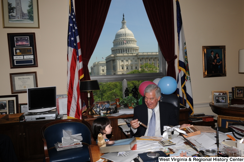 Congressman Rahall sits in his Washington office with a girl, balloons, and a cigar.