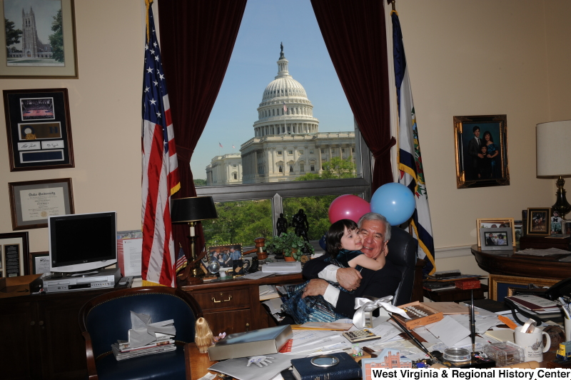 Congressman Rahall hugs a girl in his Washington office, with balloons.