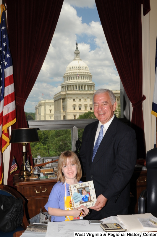 Congressman Rahall stands in his Washington office with a girl holding a scrapbook.