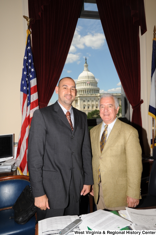Congressman Rahall stands in his Washington office with a man wearing a grey pinstripe suit.