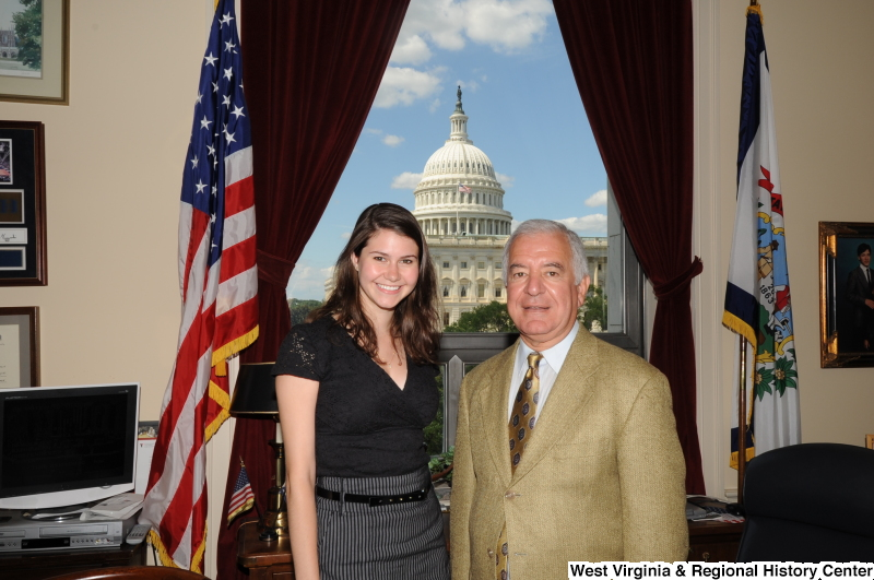 Congressman Rahall stands in his Washington office with a woman wearing a black shirt and black and white striped skirt.