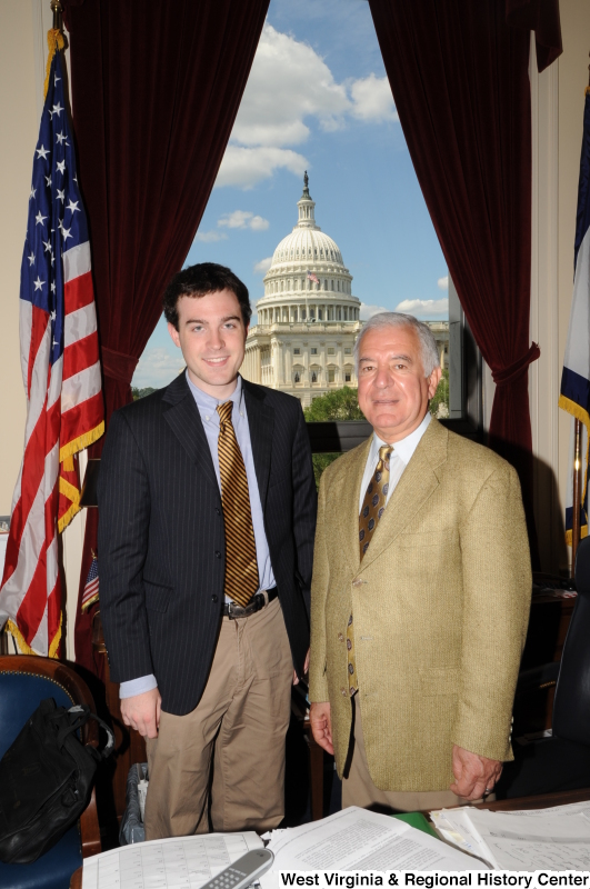 Congressman Rahall stands in his Washington office with a man wearing a dark pinstripe sport coat and gold and black striped tie.