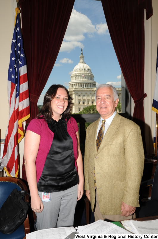 Congressman Rahall stands in his Washington office with a woman wearing a black shirt and magenta sweater.