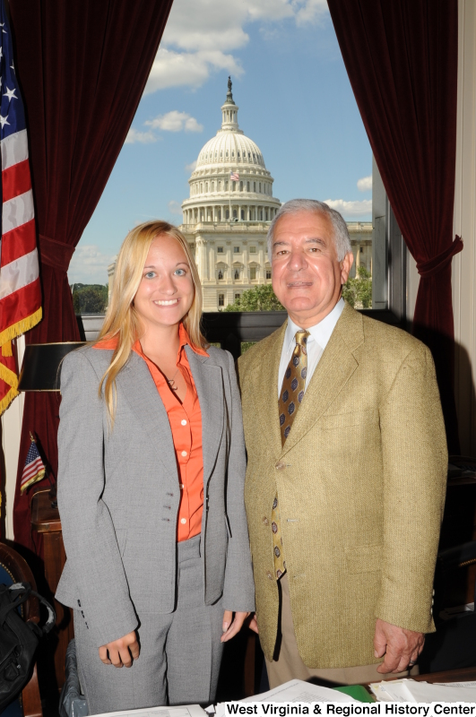 Congressman Rahall stands in his Washington office with a woman wearing a grey suit and orange shirt.