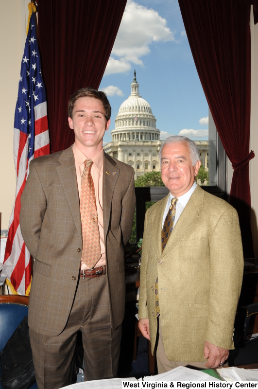 Congressman Rahall stands in his Washington office with a man wearing a brown windowpane suit.