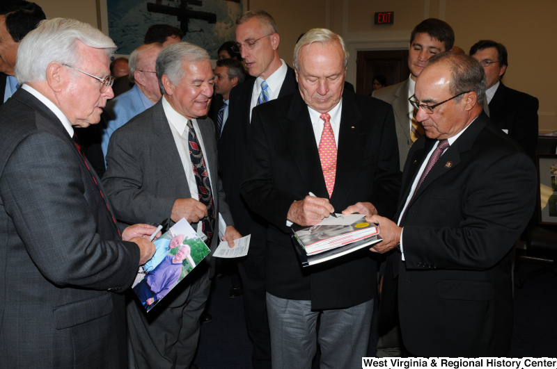Congressman Rahall and others look on while a man signs autographs.