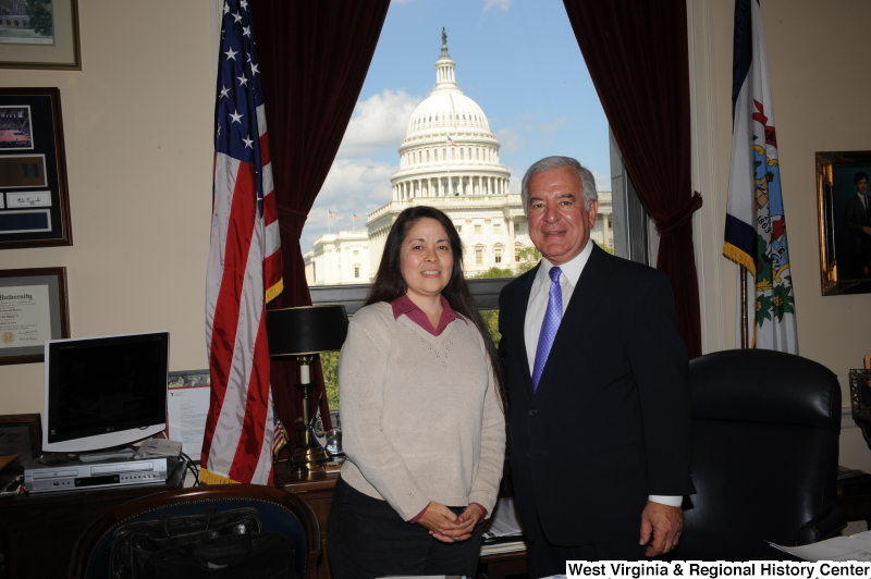 Congressman Rahall stands in his Washington office with a woman wearing a beige sweater and magenta shirt.