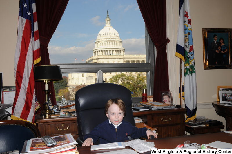 A boy sits in Congressman Rahall's chair in his Washington office.