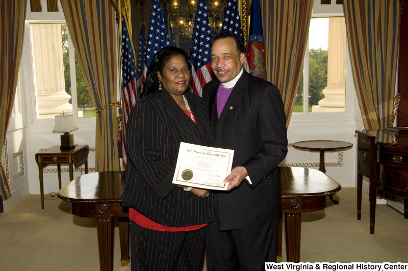 Bishop Fred T. Simms, Heart of God Ministries, Beckley, West Virginia, holds a certificate, accompanied by a woman wearing a black pinstripe suit.