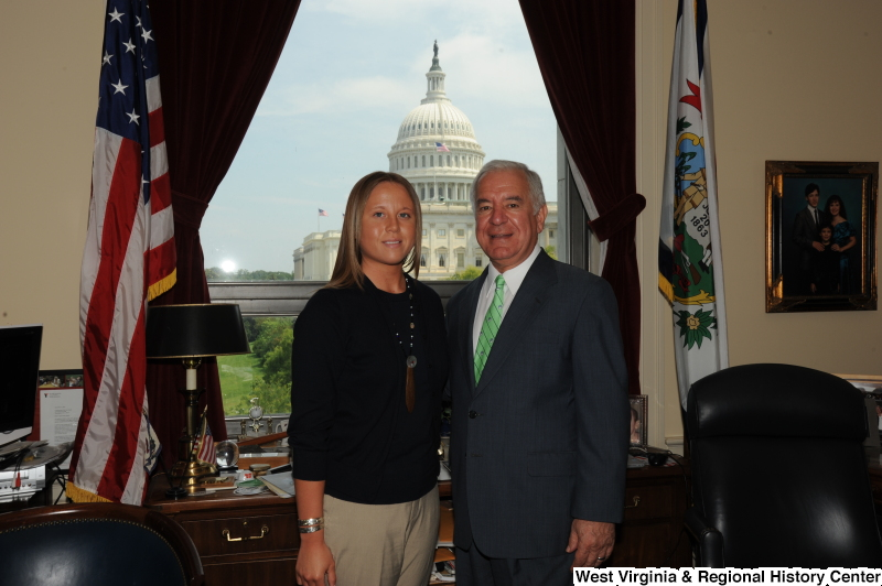 Congressman Rahall stands in his Washington office with a woman wearing a black shirt and necklace.