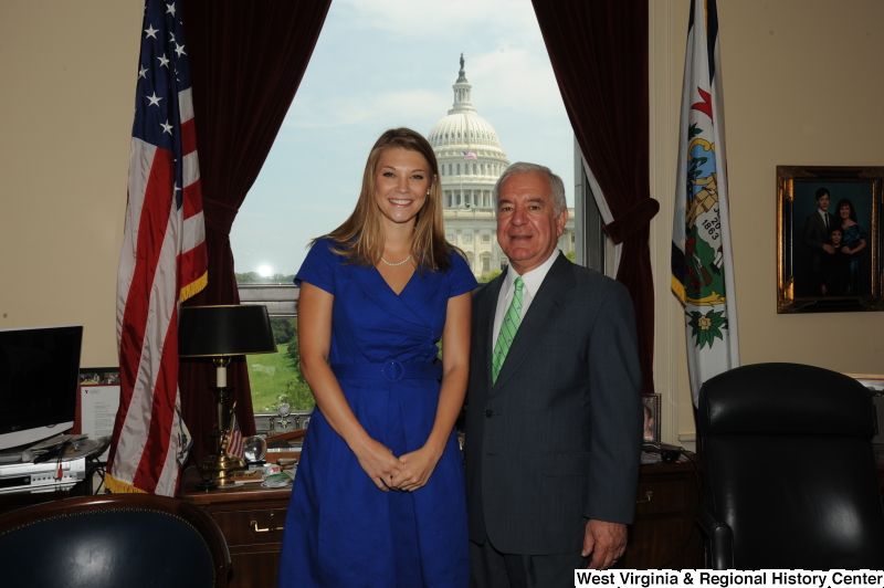 Congressman Rahall stands in his Washington office with a woman wearing a blue dress.
