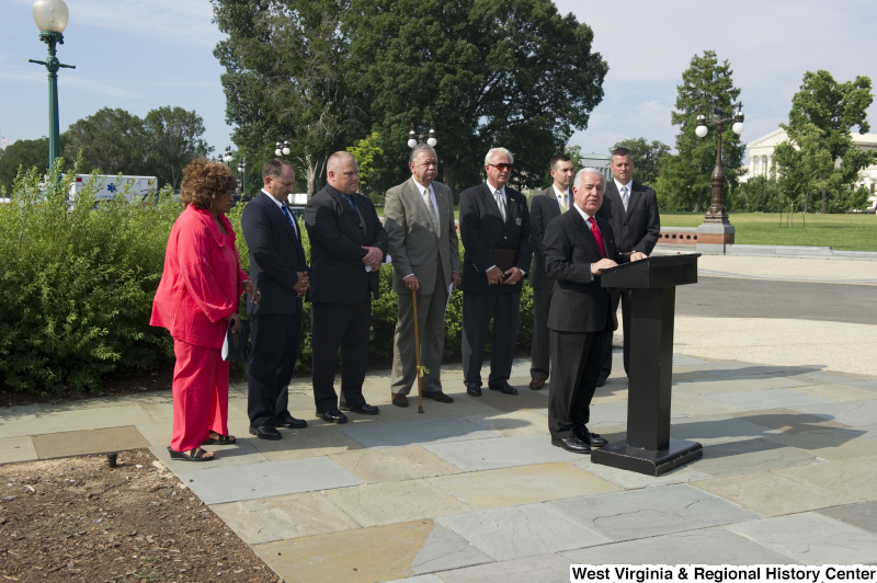 Congressman Rahall stands at a podium with seven other people during an outdoor press conference.