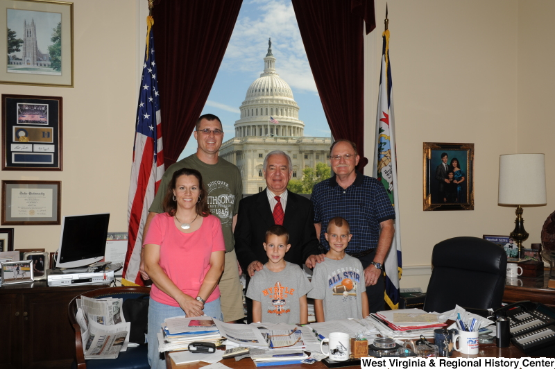 Congressman Rahall stands in his Washington office with two men, a woman, and two boys.