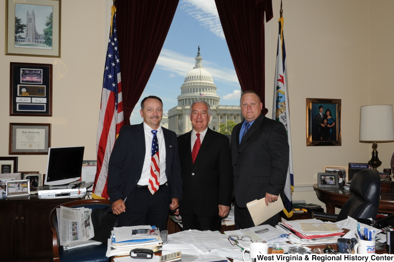 Congressman Rahall stands in his Washington office with two men, one of whom wears a United States flag-patterned tie.