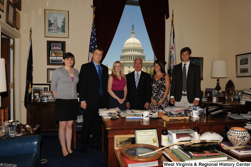 Congressman Rahall stands in his Washington office with two men and three women.