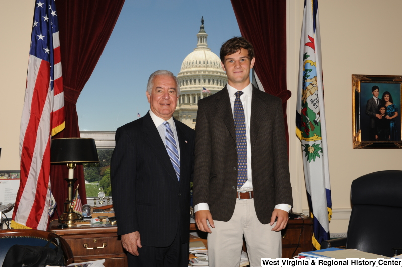 Congressman Rahall stands in his Washington office with a young man wearing a brown blazer and blue patterned tie.