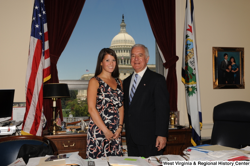 Congressman Rahall stands in his Washington office with a young woman wearing a ribbon-patterned dress.