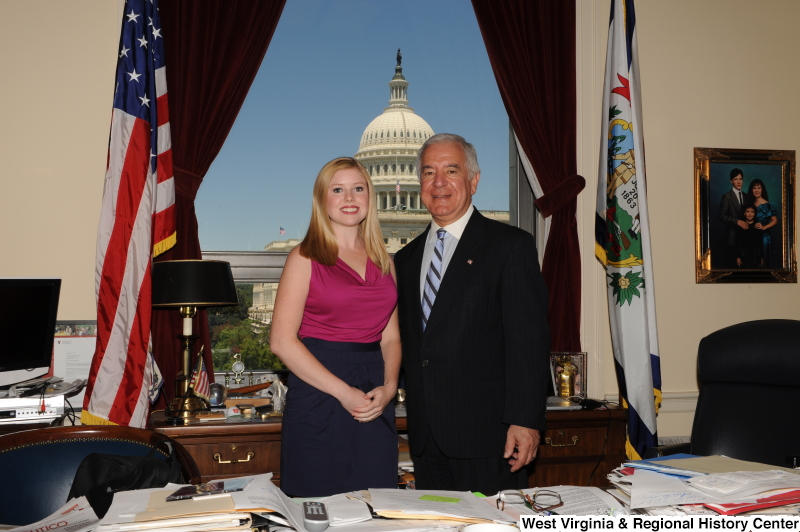 Congressman Rahall stands in his Washington office with a young woman wearing a magenta top.