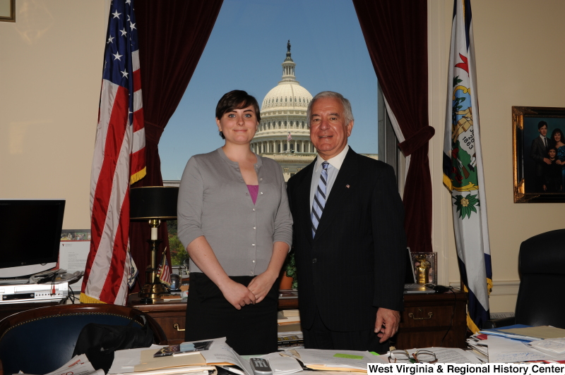 Congressman Rahall stands in his Washington office with a woman wearing a grey cardigan.