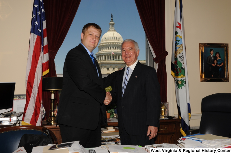 Photograph of Congressman Rahall standing in his Washington office with a man wearing a dark suit and blue tie and shirt
