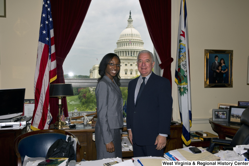 Congressman Rahall stands in his Washington office with a woman wearing a grey suit.