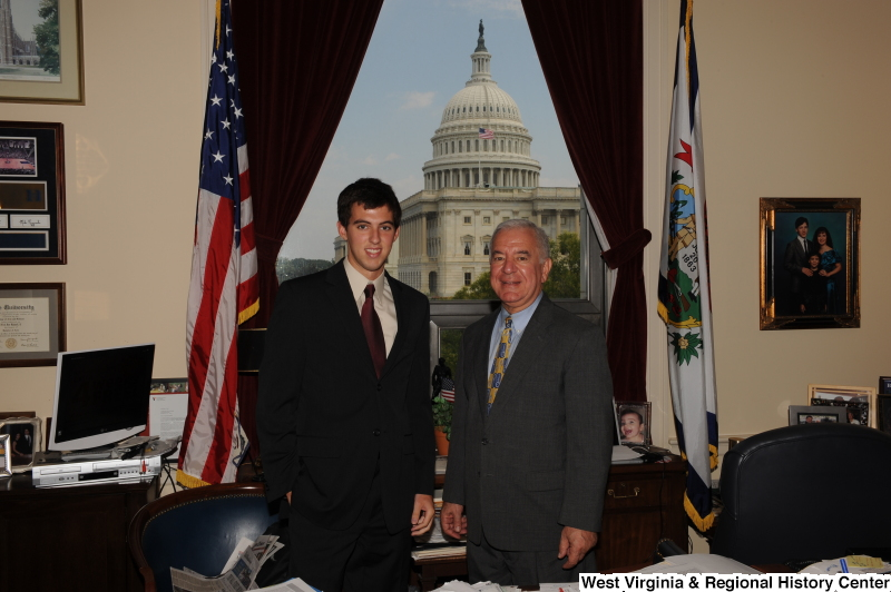 Congressman Rahall stands in his Washington office with a man wearing a dark suit and burgundy tie.