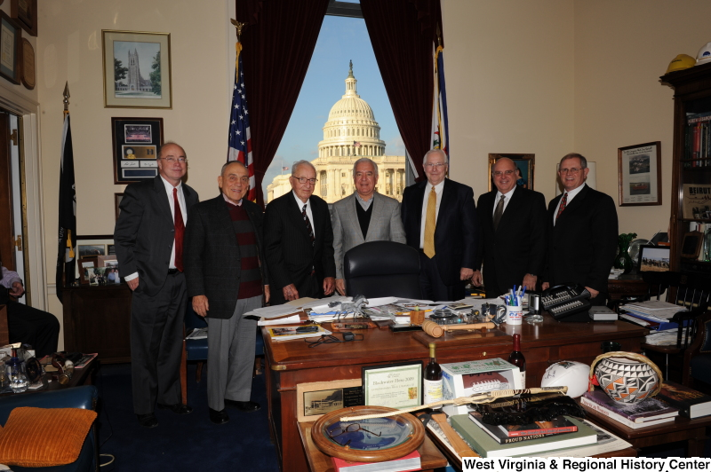 Congressman Rahall stands in his Washington office with six men.
