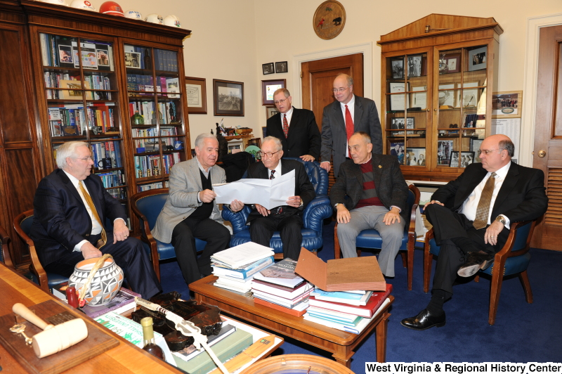 Congressman Rahall looks at a document with six men in his Washington office.