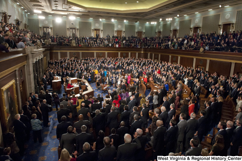 Members of the 112th Congress stand on the House floor with right hands raised.