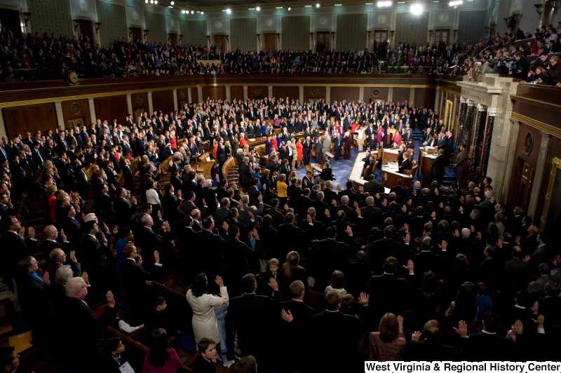 Members of the 112th Congress stand on the floor of the House of Representatives with right hands raised.