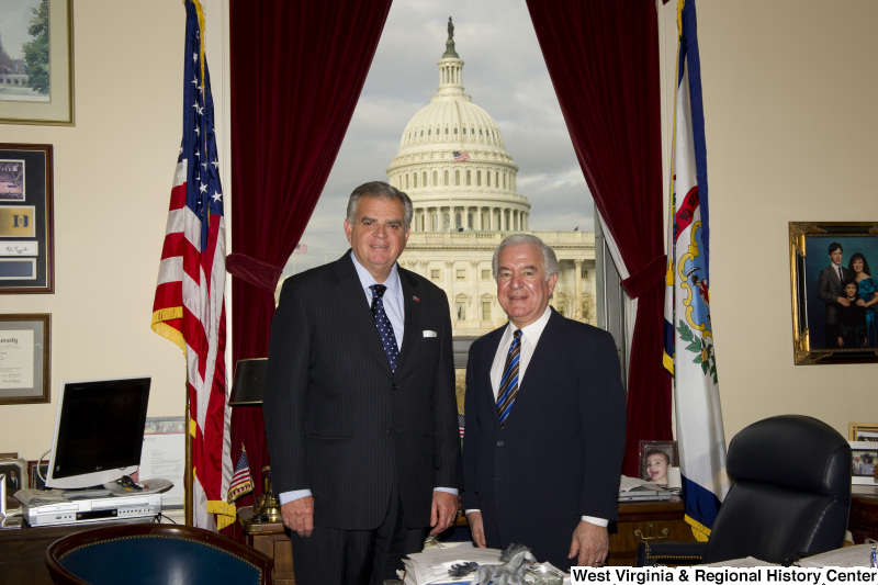 Congressman Rahall stands in his Washington office with a man wearing a dark pinstripe suit and blue and white spotted tie.