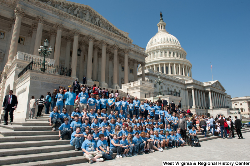 "Congressman Rahall stands on the steps of the Capitol Building with children and adults wearing blue ""Bradley"" shirts."