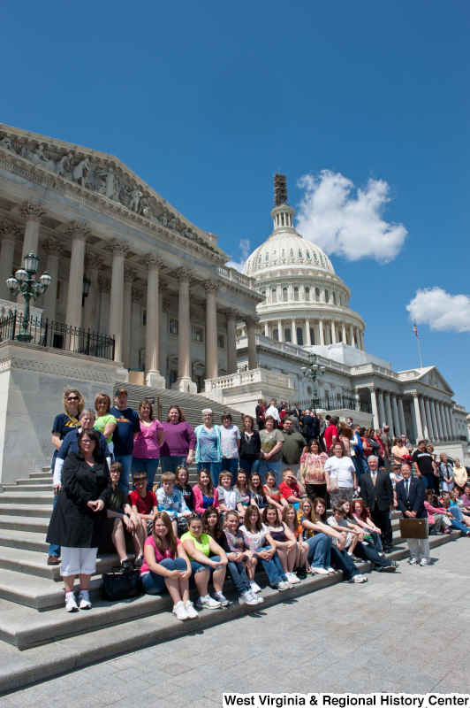 Congressman Rahall stands on the steps of the Capitol Building with adolescents and adults.