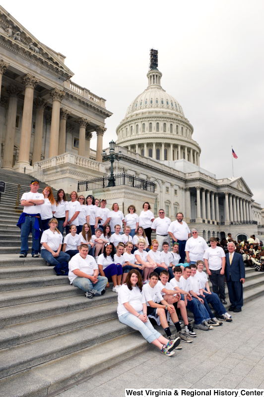 Congressman Rahall stands on the steps of the Capitol Building with adolescents and adults wearing white shirts.