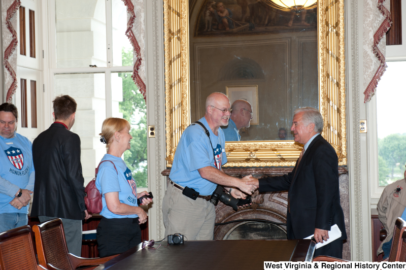 "Congressman Rahall shakes hands with people wearing ""Honor Flight"" shirts at a military award ceremony."