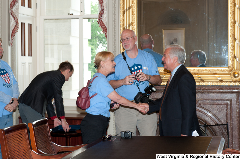 "Congressman Rahall shakes hands with men and women wearing ""Honor Flight"" shirts at a military award ceremony."