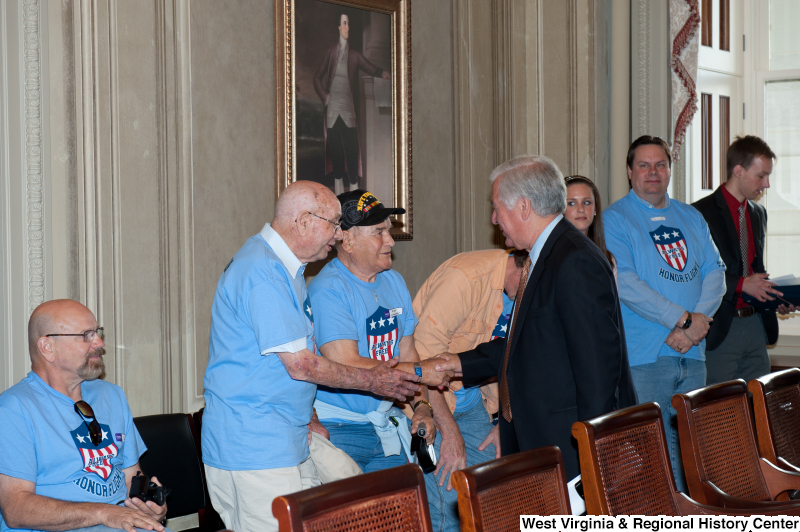 "Congressman Rahall shakes hands with men wearing ""Honor Flight"" shirts at a military award ceremony."