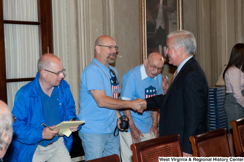 "Congressman Rahall shakes hands with men wearing red, white, and blue ""Honor Flight"" shirts at a military award ceremony."