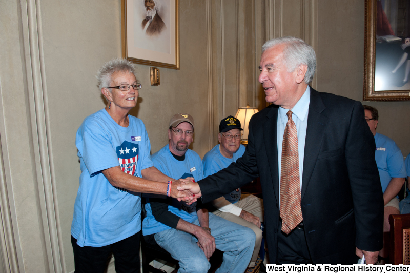 Congressman Rahall shakes hands with a woman at a military award ceremony.