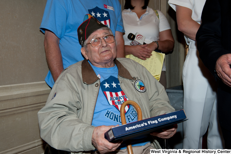 Andrew Semonco, World War II veteran, receives a certificate at a military award ceremony.
