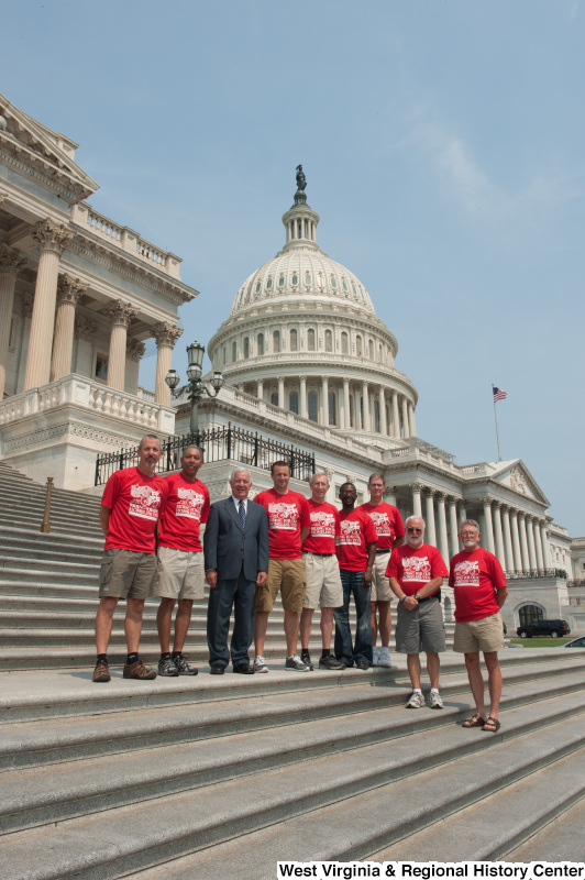 "Congressman Rahall standing on the steps of the Capitol Building with men wearing red shirts labeled ""RIDING FOR OUR HOMELESS VETS: Huntington WV to Washington DC""."