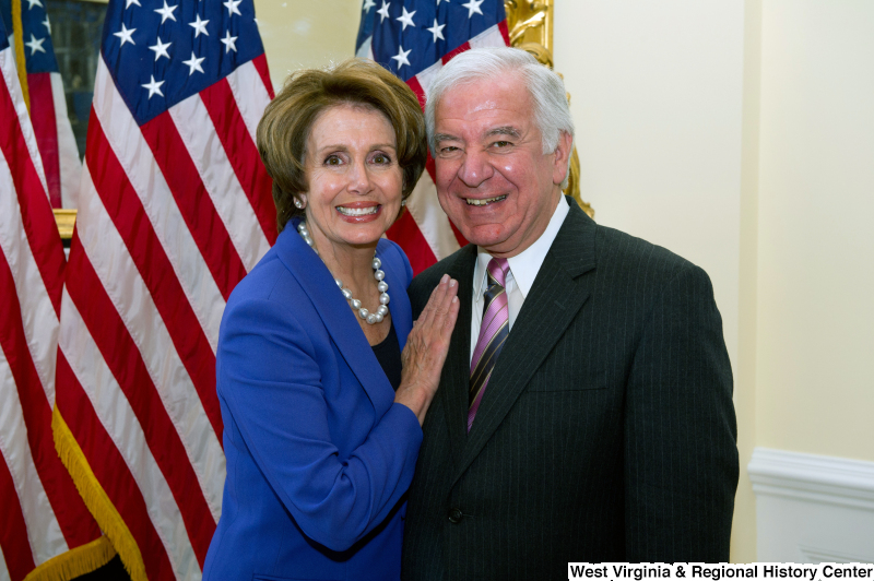 Congressman Rahall and Nancy Pelosi stand in front of United States flags.