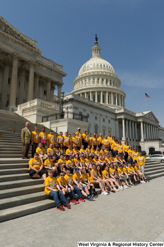"Congressman Rahall stands on the steps of the Capitol Building with children and adults wearing yellow ""Bradley Tigers"" shirts."
