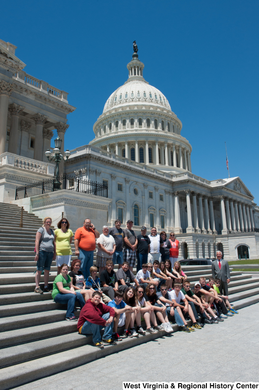 Congressman Rahall stands next to a group of children and adults on the steps of the Capitol Building.