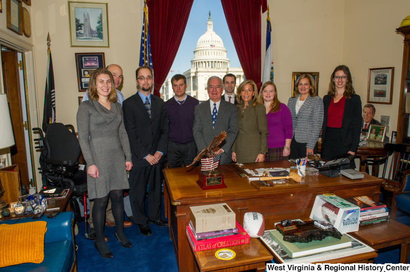 Congressman Rahall stands with a group of nine people in his Washington office.